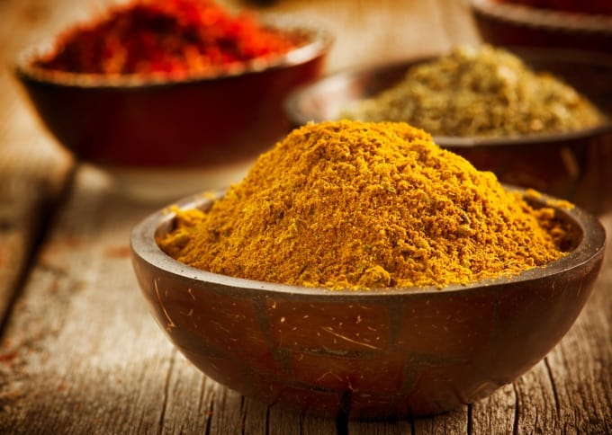 Curry powder in wooden bowl with saffron and turmeric spices in the background