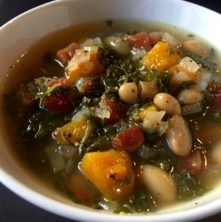 close up shot of kale butternut squash white bean soup in white bowl