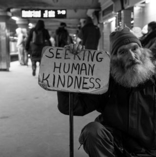 man holding seeking human kindness sign