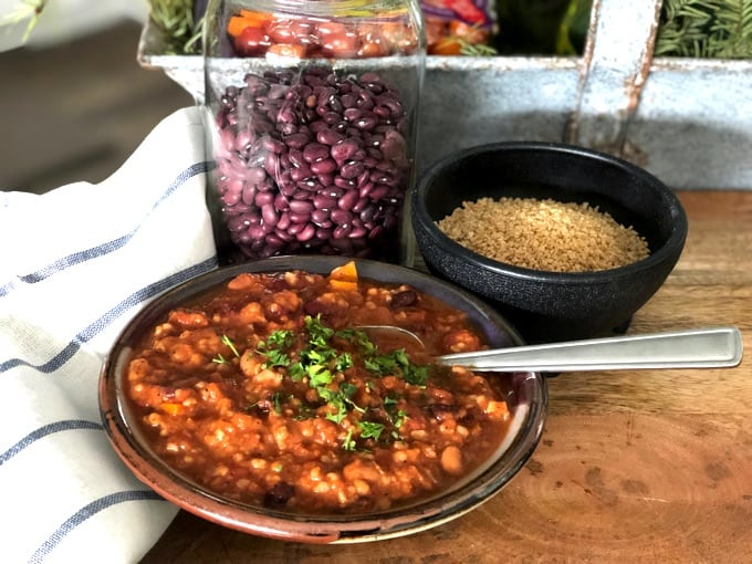 Bowl of vegetarian chili garnished with chopped parsley with dry black beans and uncooked bulgur in the background