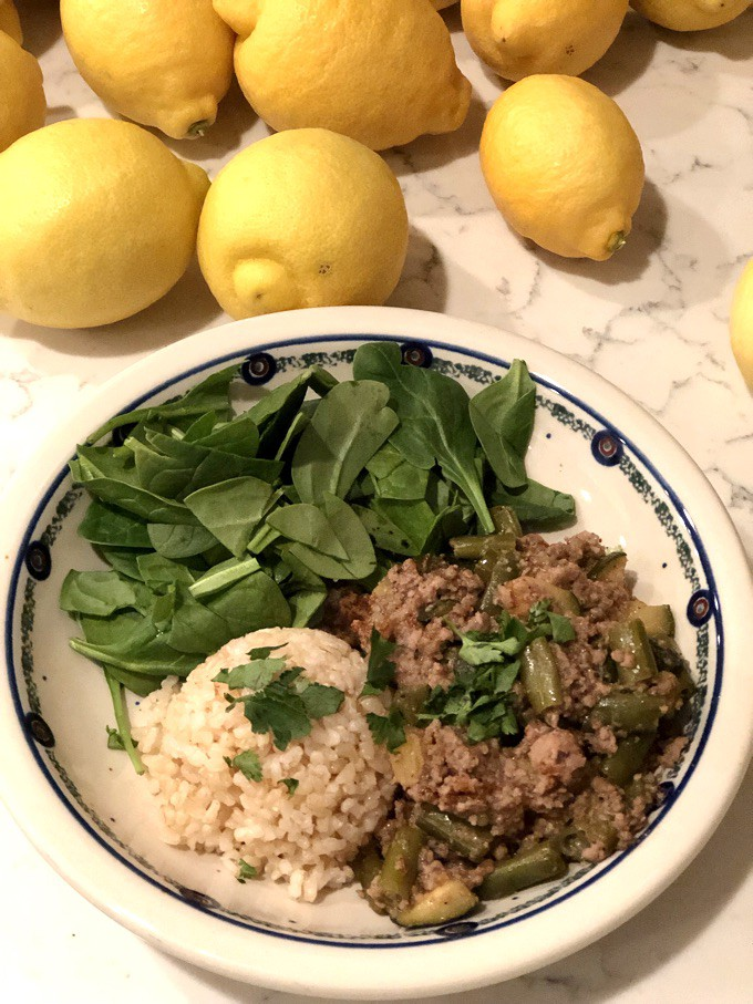 Caribbean Jerk Turkey Meal on a plate with brown rice and fresh spinach, lemons in the background