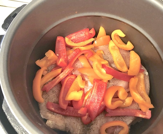 Uncooked chicken breasts topped with bell peppers in a slow cooker
