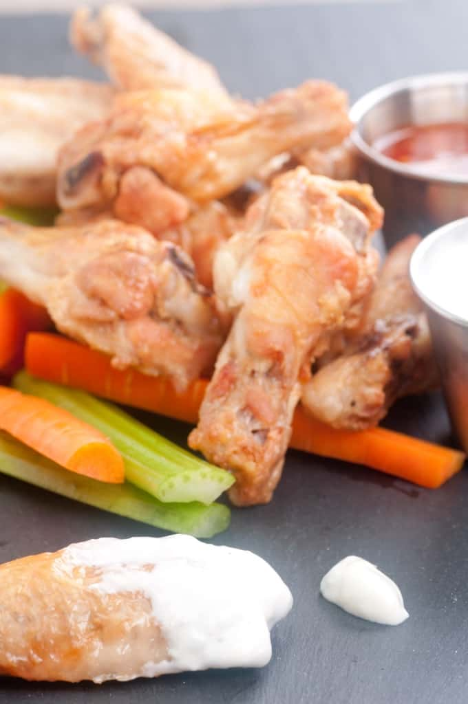 Baked healthy chicken wings with carrot and celery sticks and dipping sauce on the side