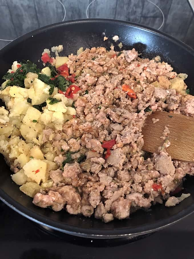 Turkey sausage cooking in a skillet with potatoes, spinach and red bell pepper