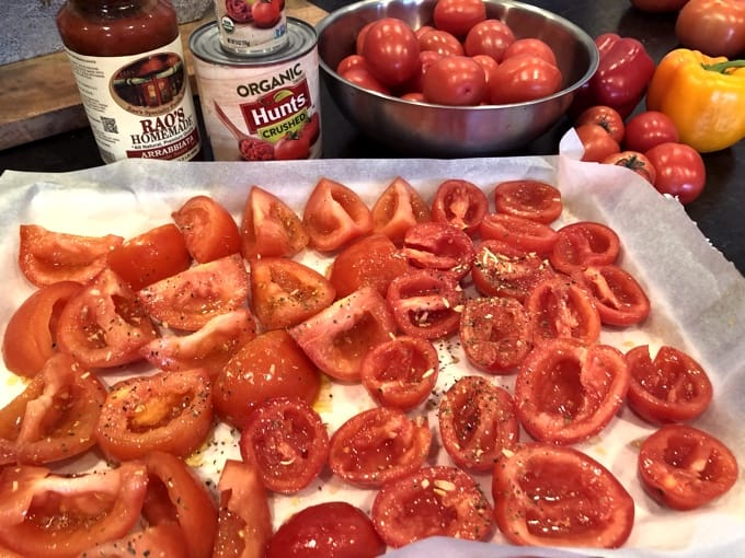 Roma tomatoes drizzled with olive oil and Italian spices on parchment-line baking sheet