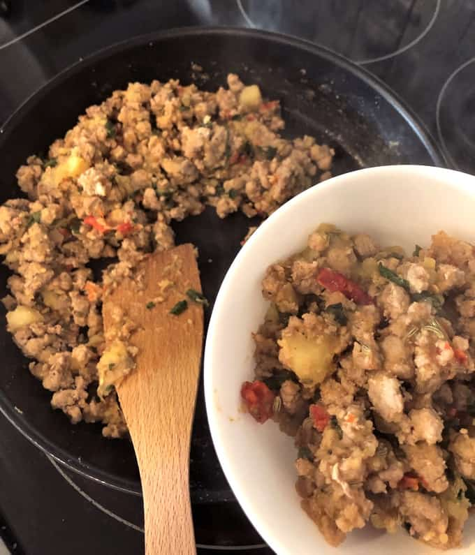 Dishing up Turkey Breakfast Sausage from skillet to a small bowl