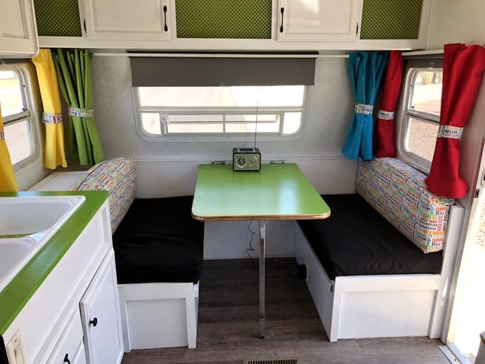 Looking inside a renovated travel trailer with lime green counter and table, bench seat and red, blue, yellow and green curtains
