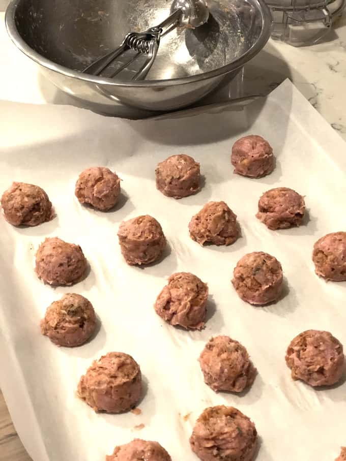 Lemon Pepper Turkey Meatballs on a parchment lined baking sheet with mixing bowl and cookie scoop in the background