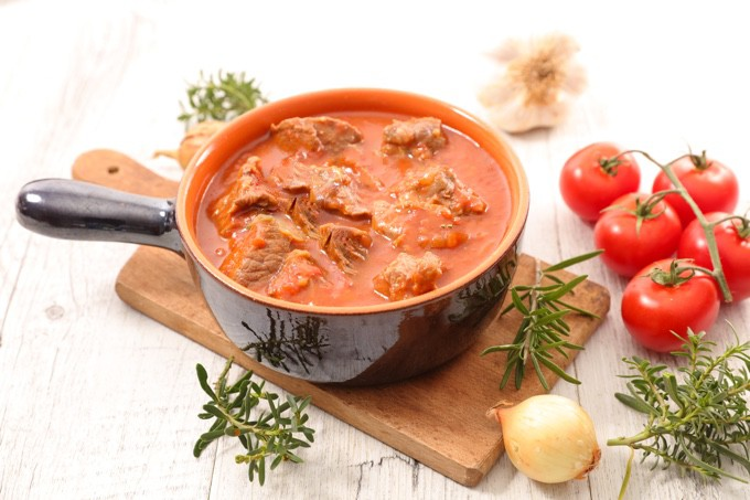 Pork Stew in a bowl on wood table with fresh tomatoes and rosemary scattered about