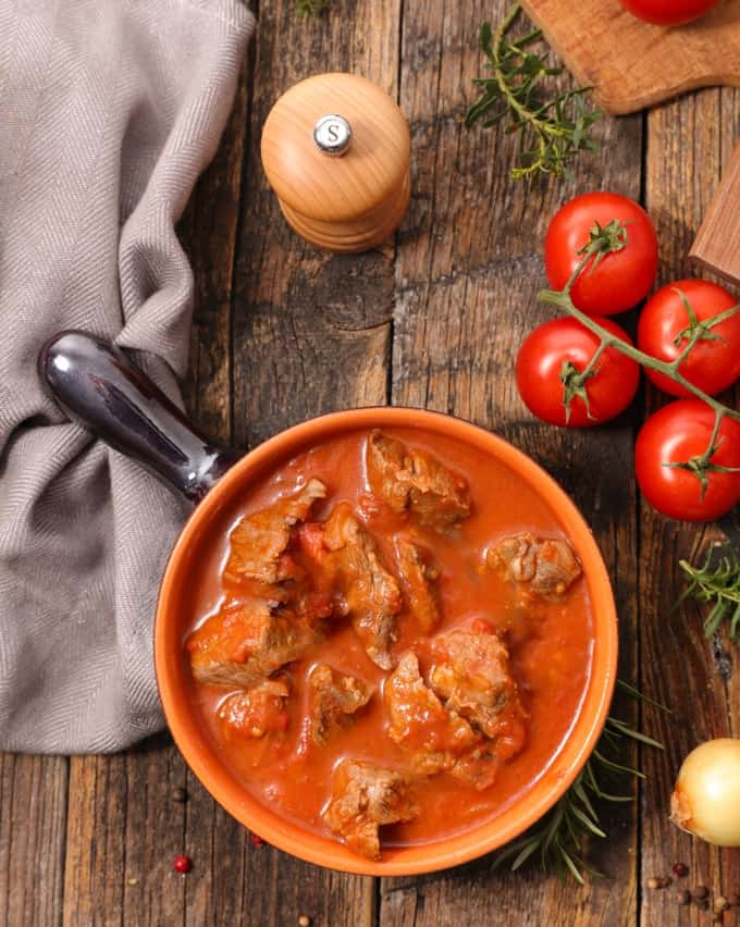Pork Sarciado stew in a bowl on a wooden table with fresh tomatoes and herbs
