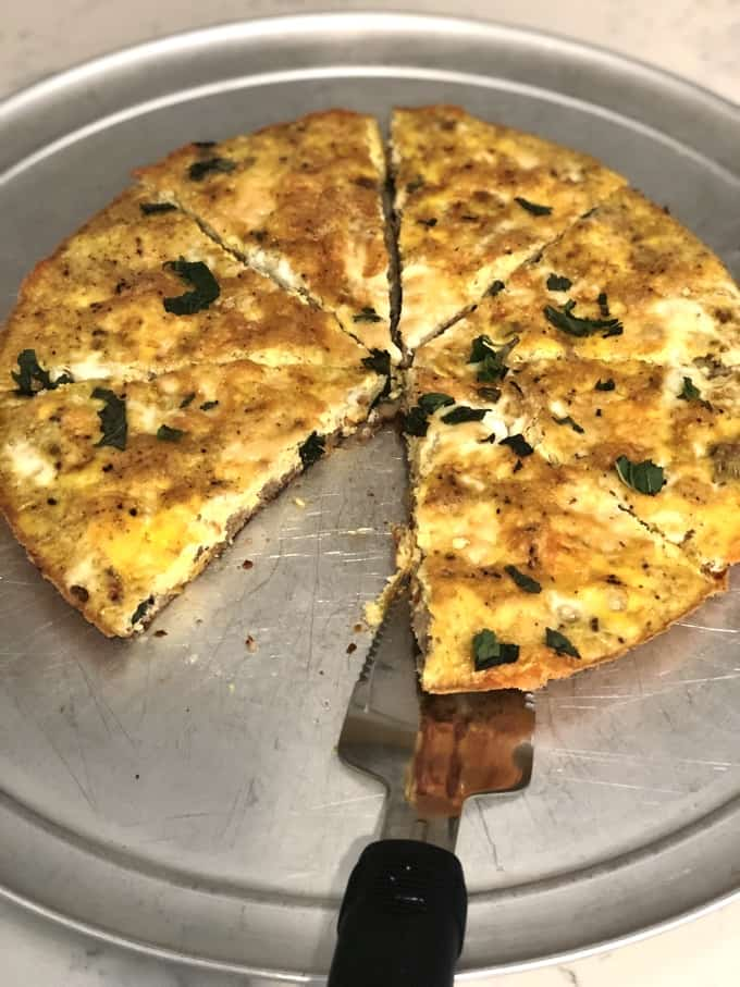 Fritatta on pizza pan cut into 8 pieces with one slice missing