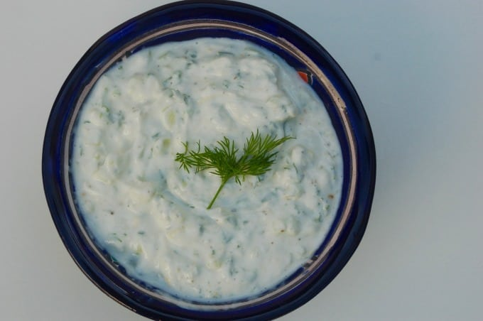 Creamy Cucumber Salad Dressing in a blue bowl garnished with fresh dill