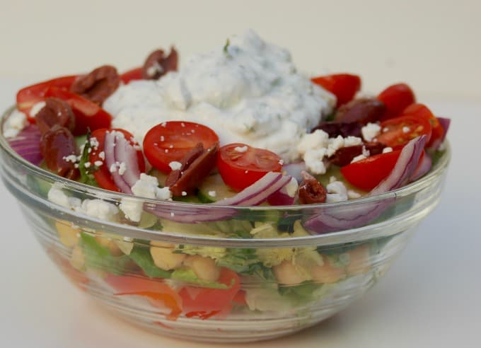 Layered Mediterranean salad with peppers, cucumber, onion, Kalamata olives, tomatoes and creamy cucumber dressing