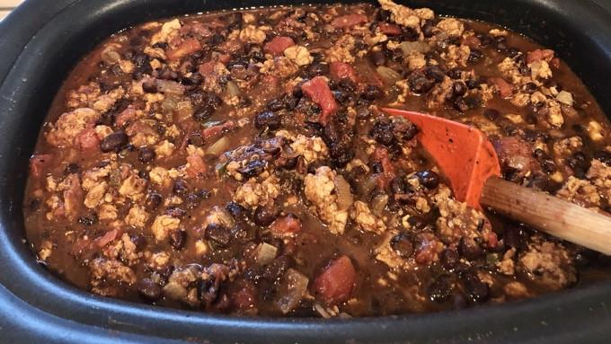 Stirring chili in Ninja multi-cooker with rubber spatula