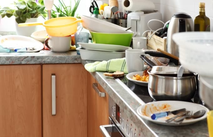 Dirty dishes piled up on a messy kitchen countertop