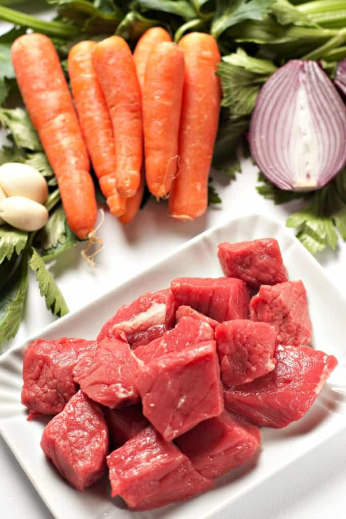 Lean cubed uncooked beef, raw carrots, garlic cloves and onion for making French beef stew