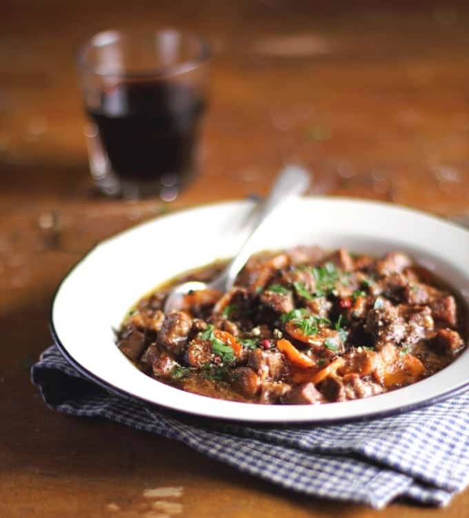 French beef stew in bowl with spoon and glass of red wine in background