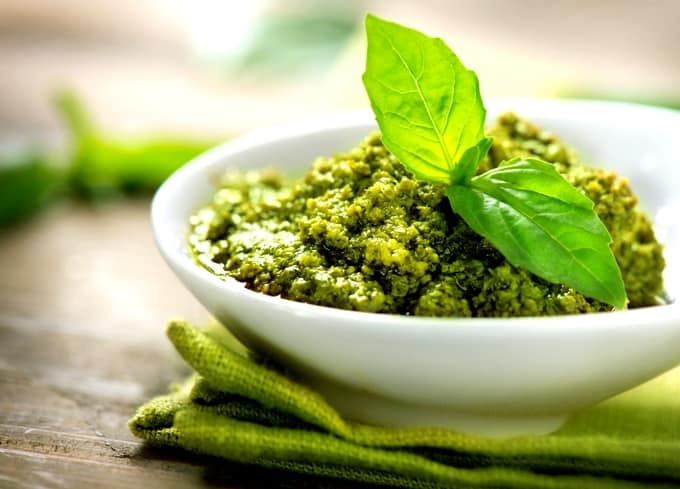 Small white bowl with basil pesto garnished with basil leaves
