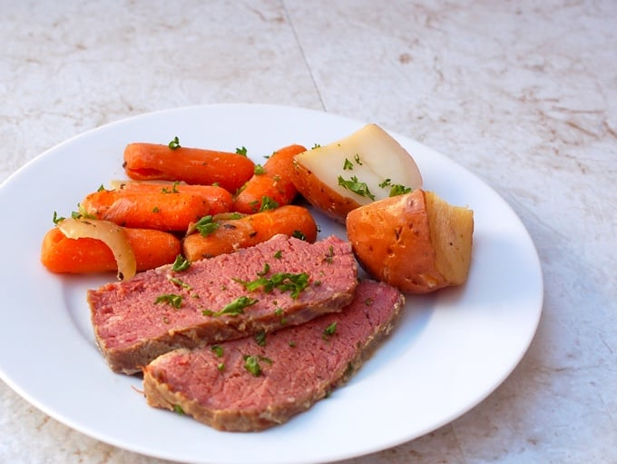 Beer Braised Corned Beef with carrots and potatoes on a dinner plate