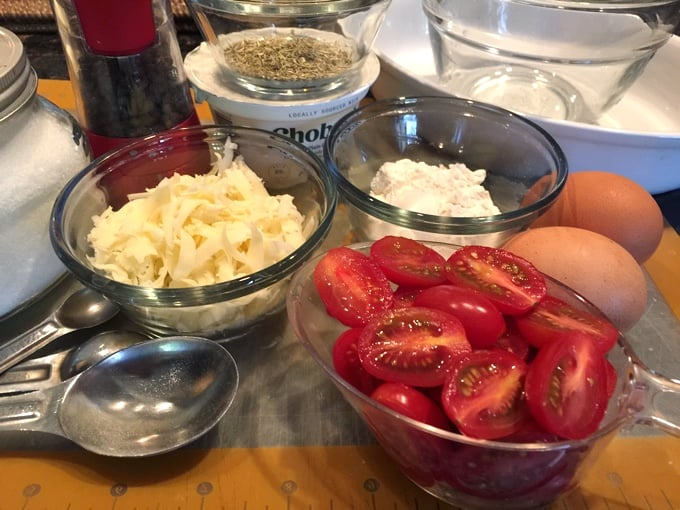 Halved cherry tomatoes, shredded cheese, Greek yogurt, eggs and herbs for making Cherry Tomato Clafoutis