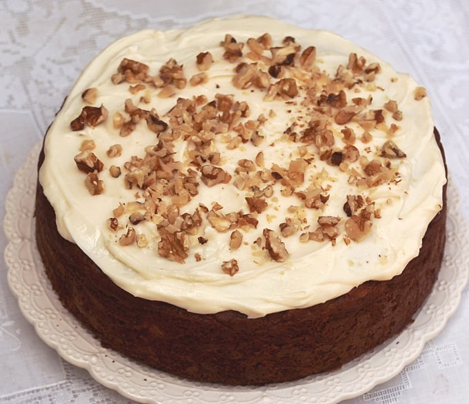 Carrot Cake with Pineapple Cream Cheese Frosting and Chopped Walnuts on serving plate