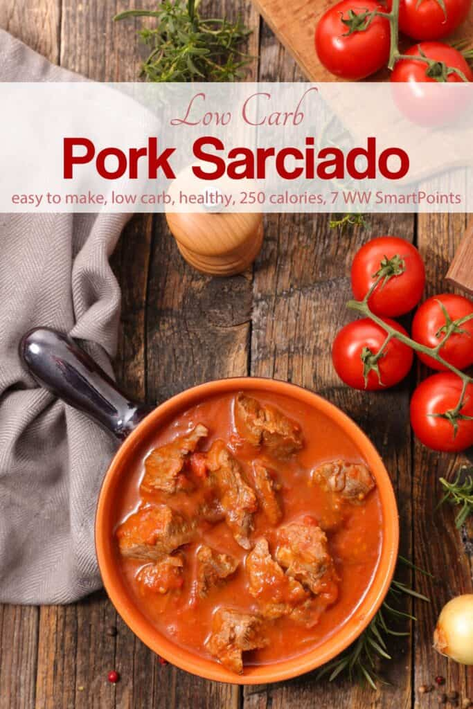 Filipino Pork Sarciado Stew in a pot on wooden table with fresh tomatoes