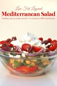 Layered Mediterranean Salad with skinny creamy cucumber dressing in a glass bowl
