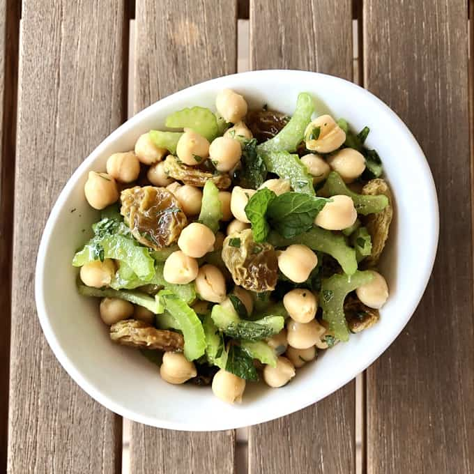 Vegetarian chickpea salad with celery and raisins in white bowl on wooden table from above.