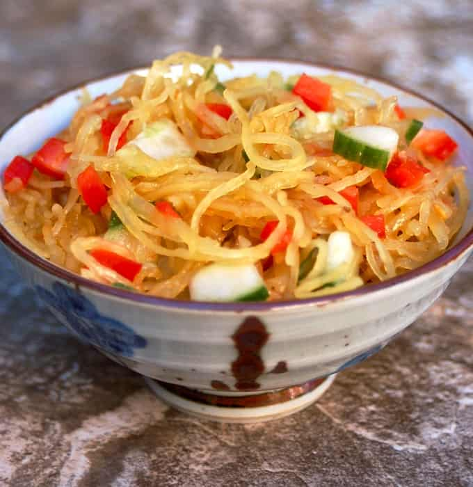 Asian spaghetti squash salad with chopped cucumber and red bell pepper in ceramic bowl.
