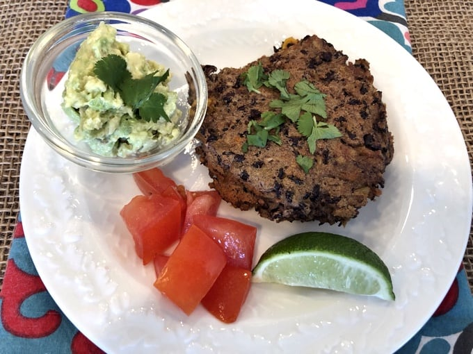 Black bean cake on white plate with lime wedge, chopped tomatoes and small bowl of guacamole.