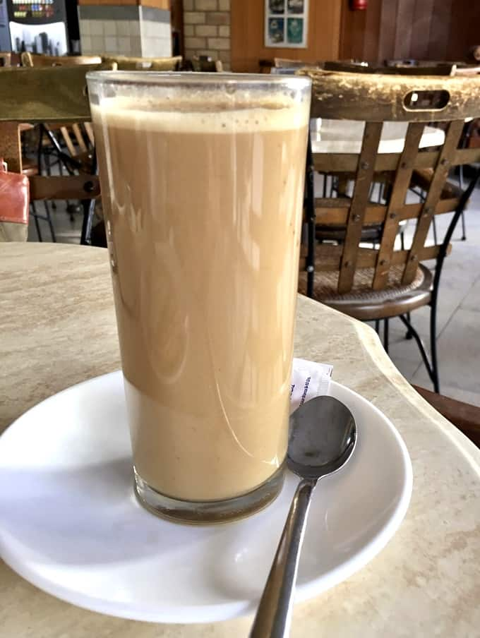 Cafe con leche on table with spoon in cafe in Rota, Spain.