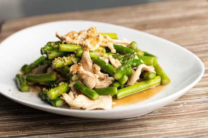 Chicken and asparagus stir fry on white dinner plate.