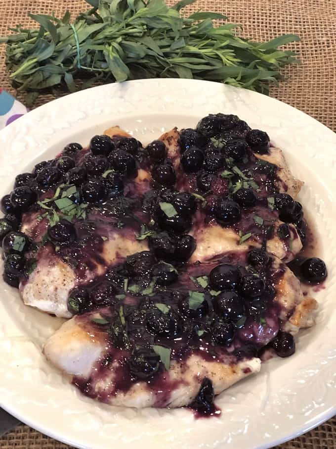 Chicken cutlets topped with fresh blueberry sauce and bunch of fresh tarragon in the background