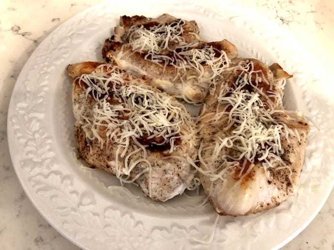 Chicken cutlets topped with shredded Fontina cheese on white plate
