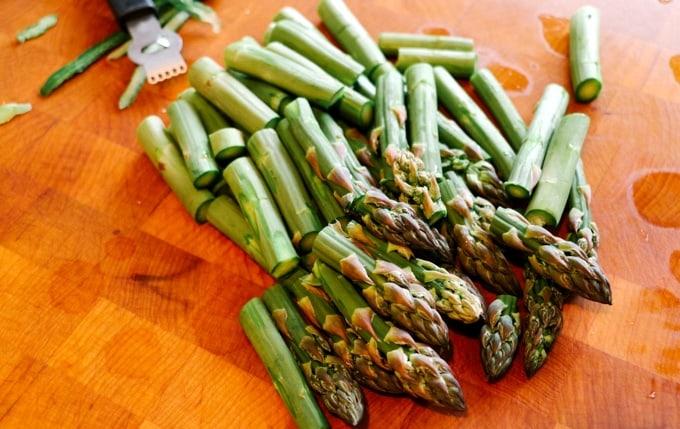 Fresh chopped asparagus spears on wood cutting board.