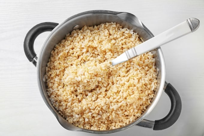 Cooked brown rice in pan with fork.