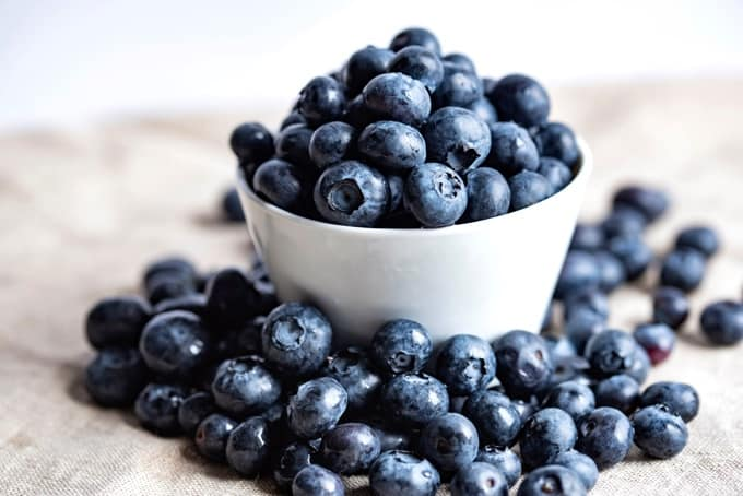 Fresh blueberries in small white bowl with loose blueberries piled outside the bowl