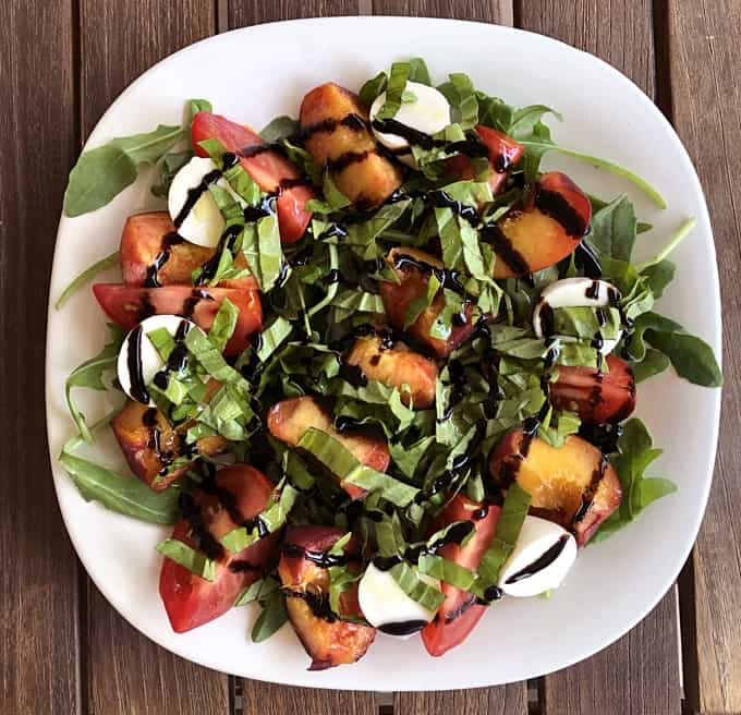 Fresh tomato and peach caprese salad with balsamic drizzle on square white plate.