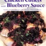 Chicken breast cutlets topped with fresh blueberry sauce and tarragon on white serving plate
