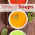 Three bowls of creamy soup including tomato soup, squash soup and zucchini soup on wooden table with fresh herbs.