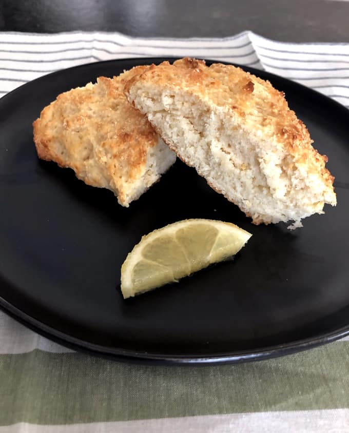 Lemon scones on black plate with lemon wedge