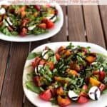 Two peach tomato caprese salads on white plates on wooden table.