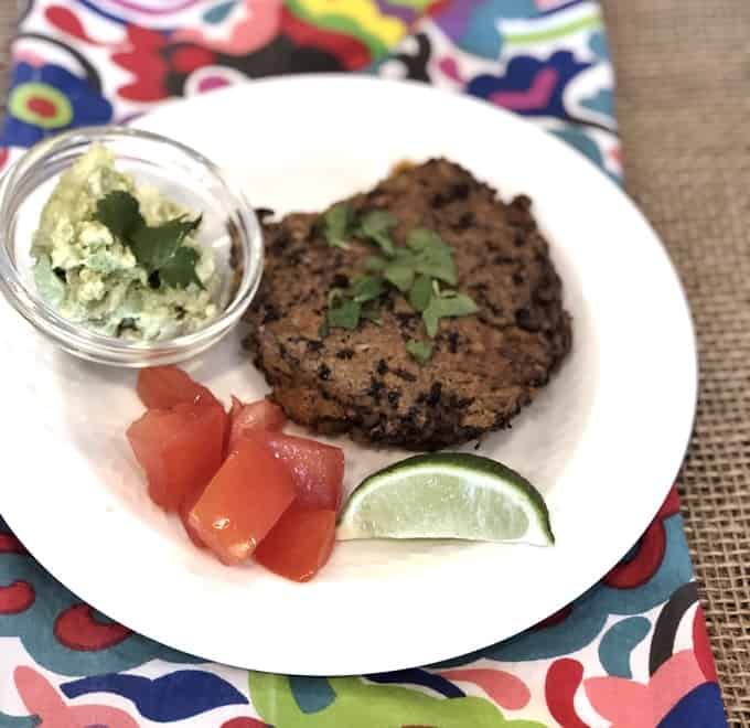 Vegetarian black bean burger on white plate with chopped tomatoes, lime wedge and small bowl of guacamole.