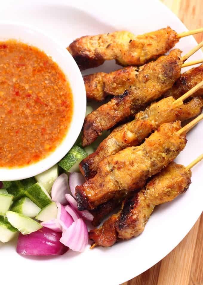 Chicken satay skewers with spicy peanut sauce on the side.