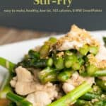 Chicken and asparagus stir fry up close on white dinner plate.