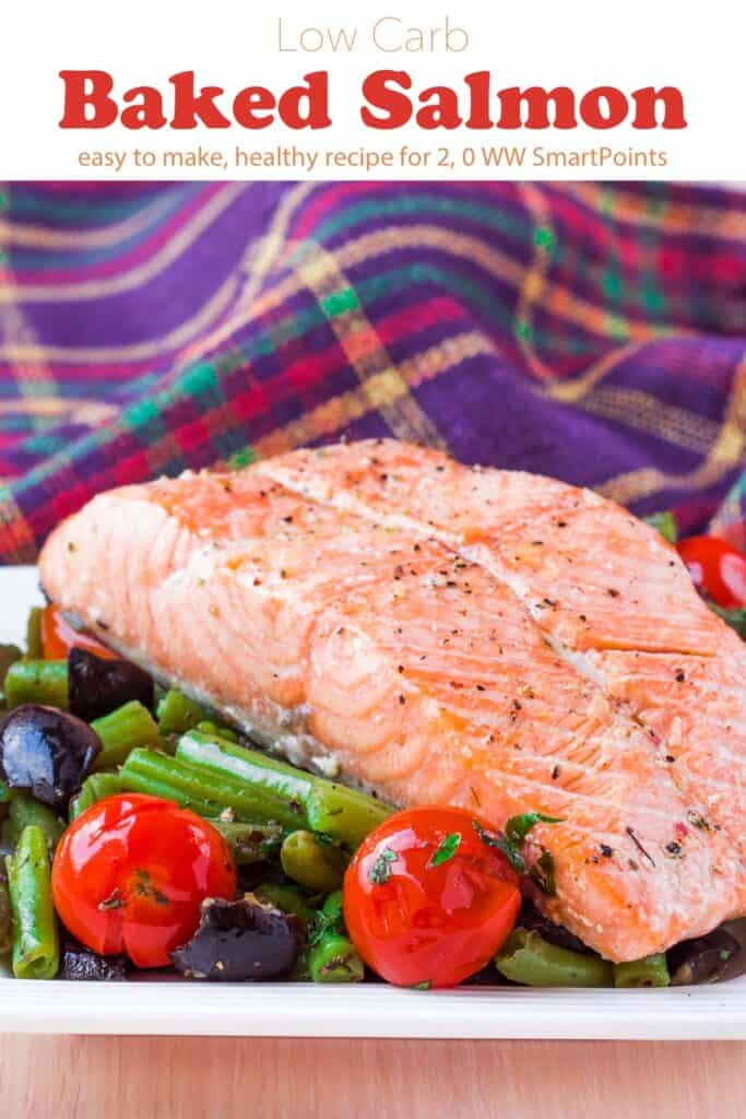 Baked salmon on white plate with tomatoes, olives and green beans.