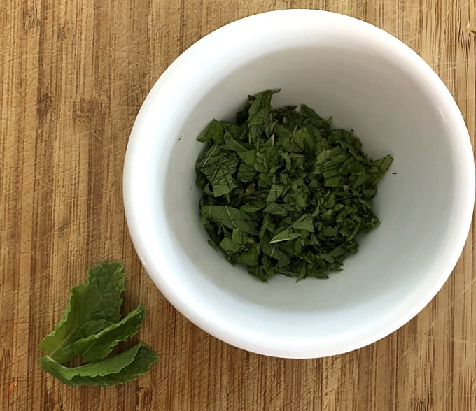 Fresh chopped mint leaves in small white bowl.