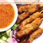 Chicken satay skewers on white plate with spicy peanut dipping sauce and fresh vegetables.