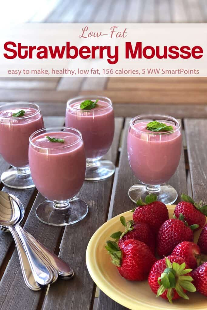 Creamy Strawberry Mousse topped with fresh mint near a plate with whole fresh strawberries.