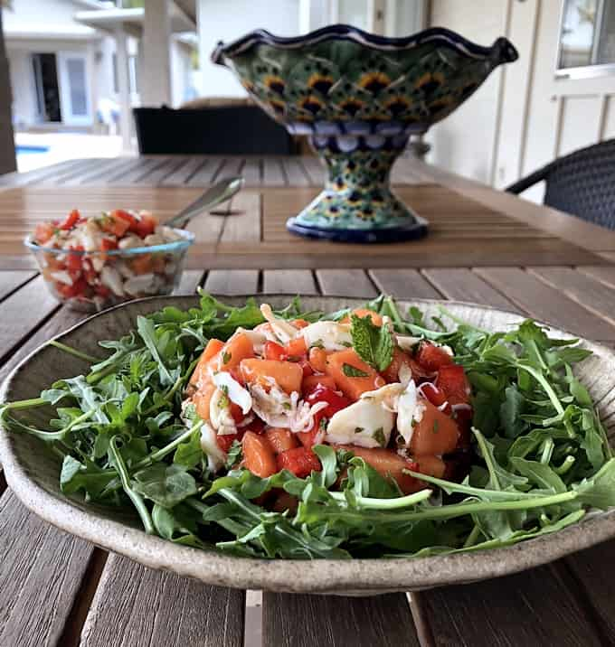 Papaya crab salad on bed of arugula with small bowl of crab salad in the background.